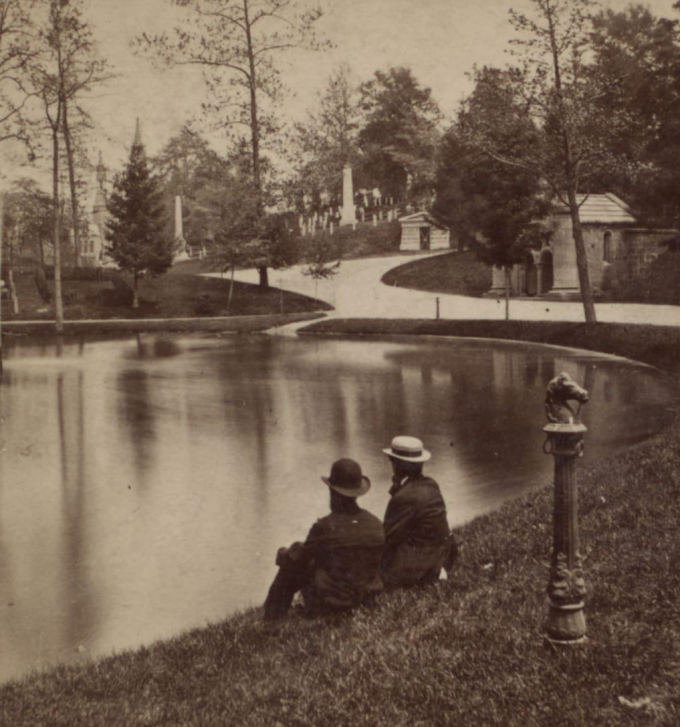 Two men seated by a serene pond in Green-Wood Cemetery