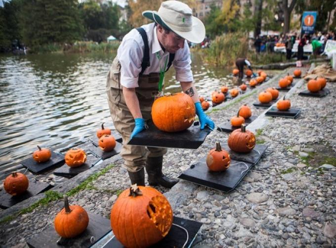Worker preparing floating jack-o-lanterns