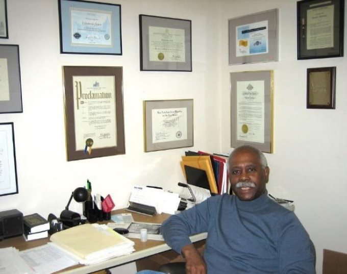 Cal Jones at his desk with framed credentials on two walls