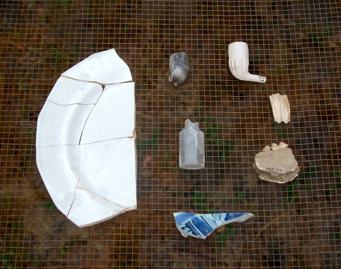 Excavated shards of kitchenware, a smoking pipe, and a bottle